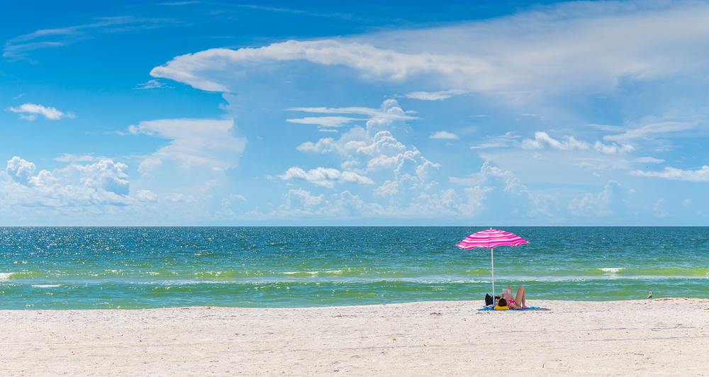 A couple under an umbrella on St Pete's beach. One of the best florida beaches for couples