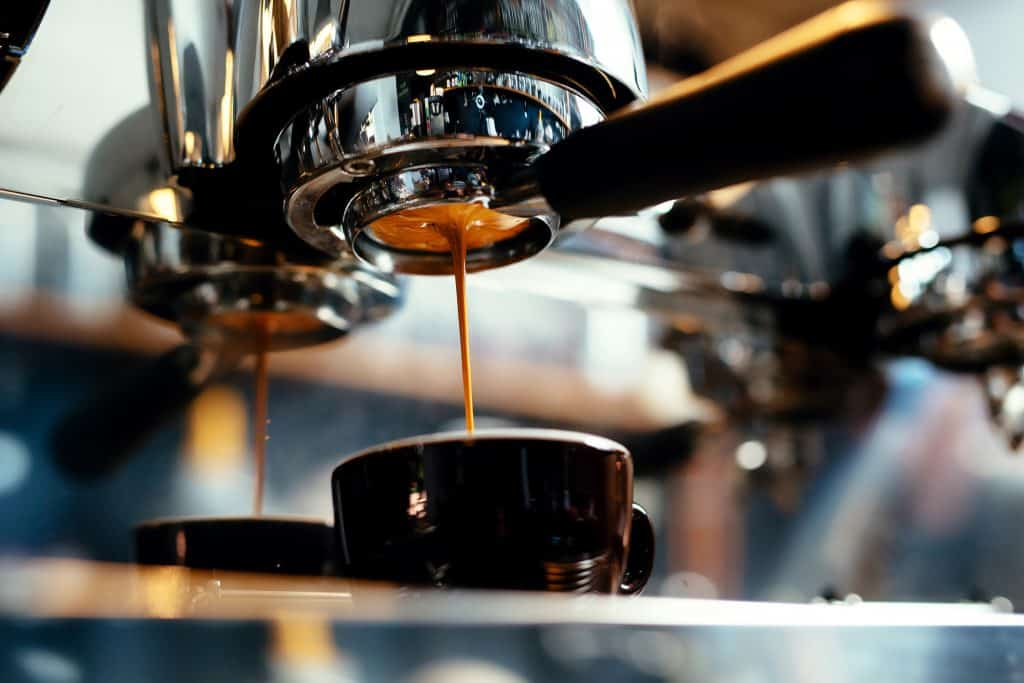Espresso pours from the machine into the shot glass.