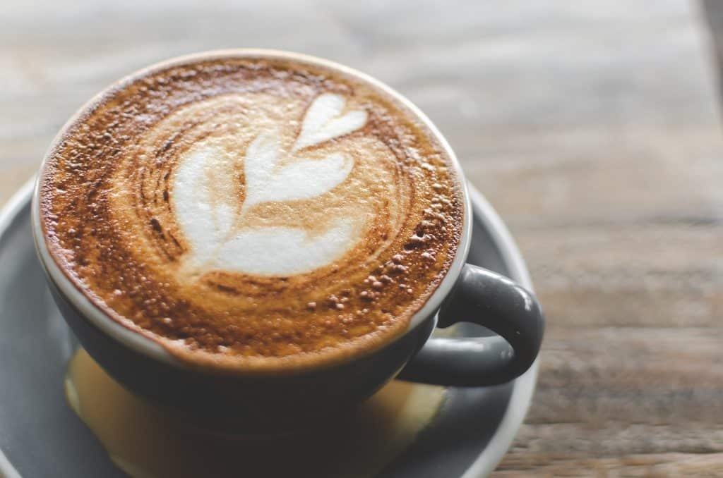 An espresso machiatto is served with a heart design, made with the best coffee in Miami.
