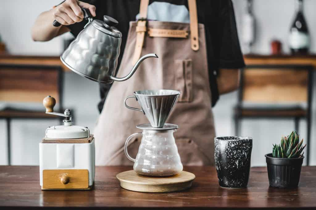 A barista pours hot water over a chemex, a brewing method to produce the best coffee in Miami.
