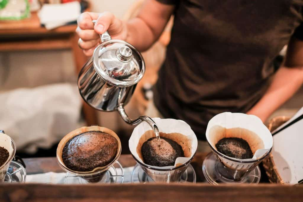 A barista pours hot water in the pour over method of brewing, producing the best coffee in Miami.