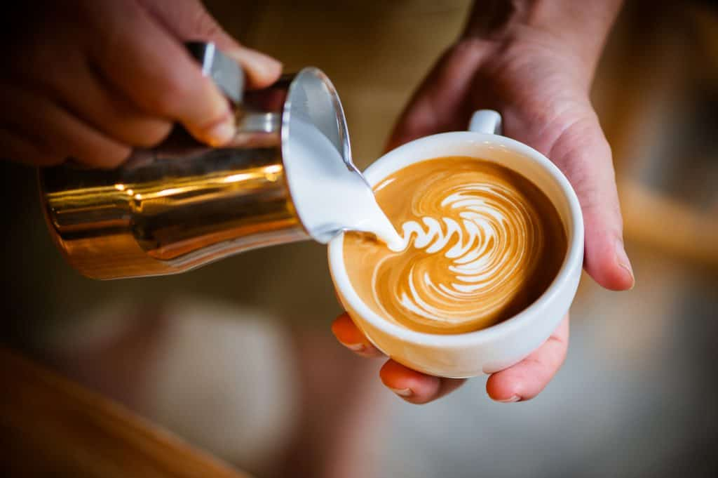A barista pours velvety microfoam into rosetta design over espresso.