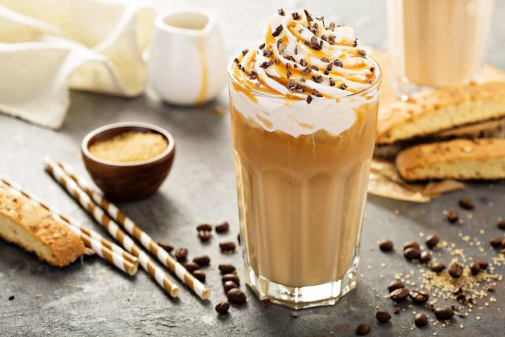 An iced coffee is topped with whipped cream, caramel and chocolate chips.