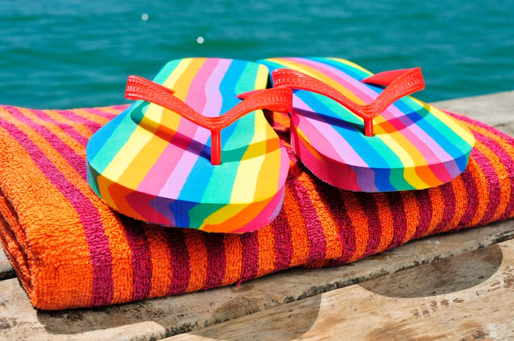 Rainbow flip flops on a towel in an article about gay beaches in Florida
