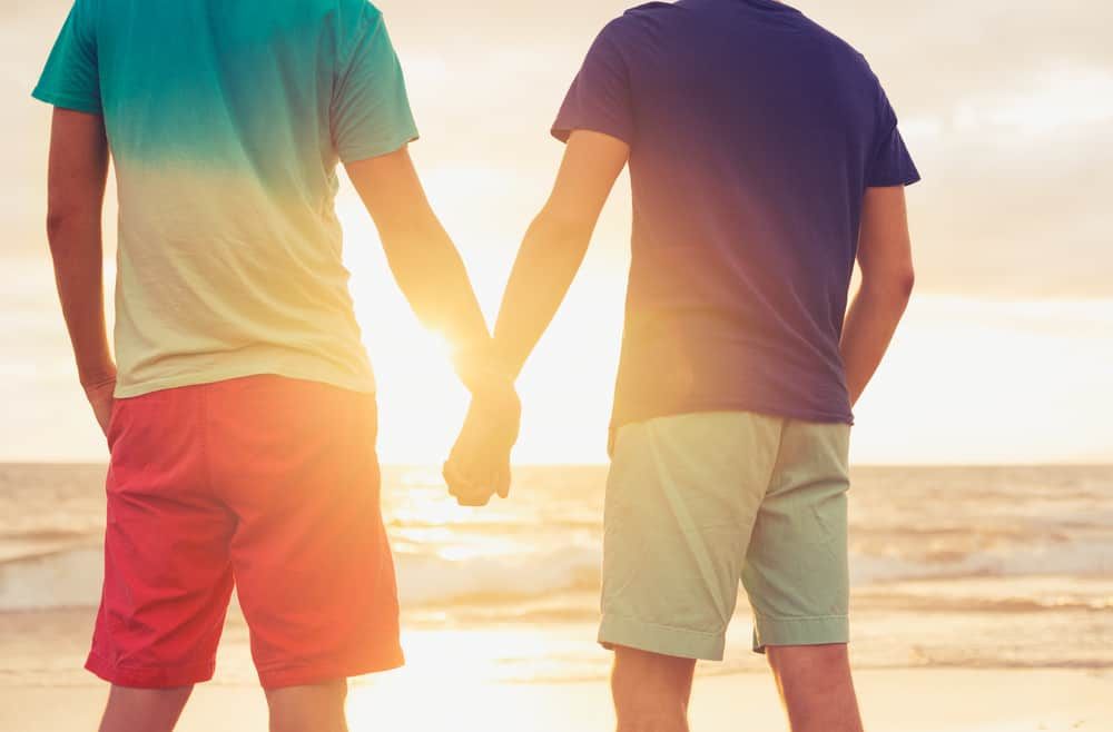 Gay couple holding hands on a beach