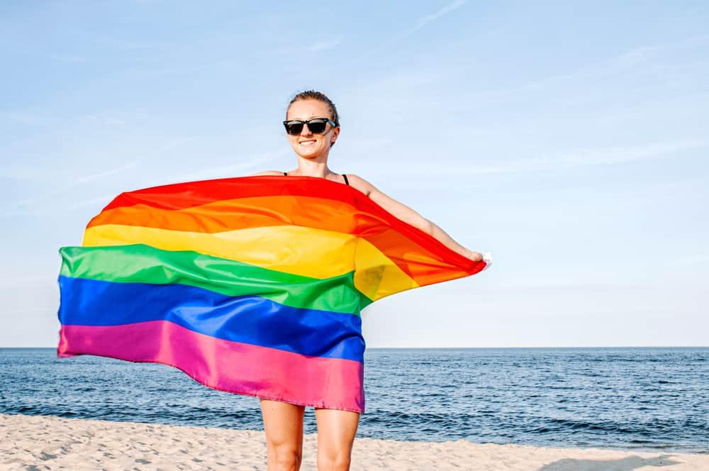 Girl holding a rainbow flag on a beach