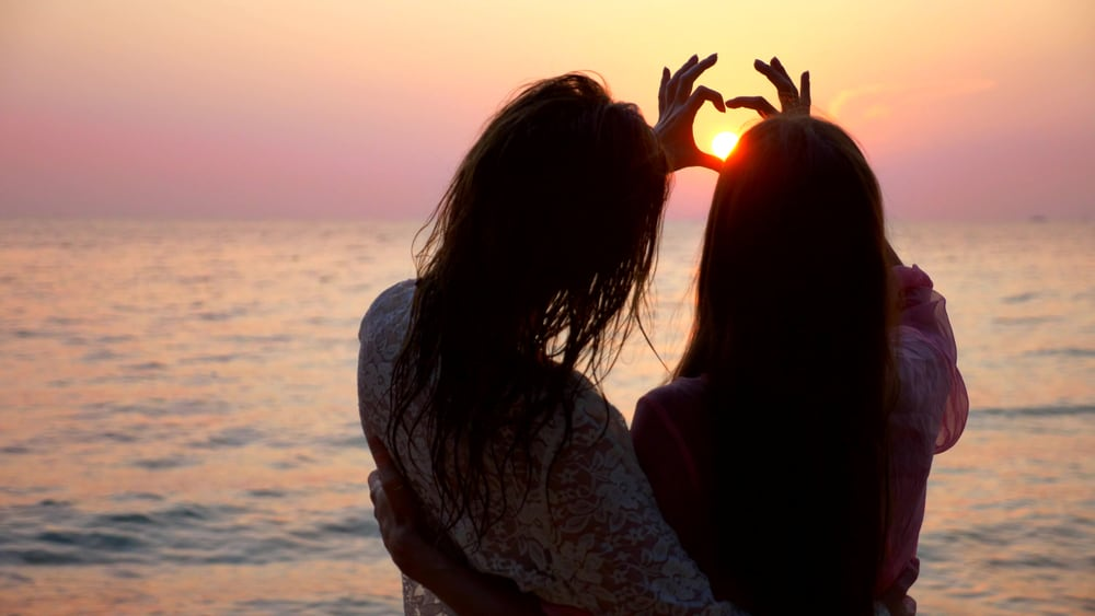 Two girls on a beach together in an article about gay beaches
