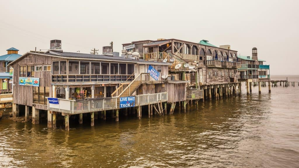 Fishing, bait, and tackle shops hover over the water on stilts in Cedar Key, Florida.