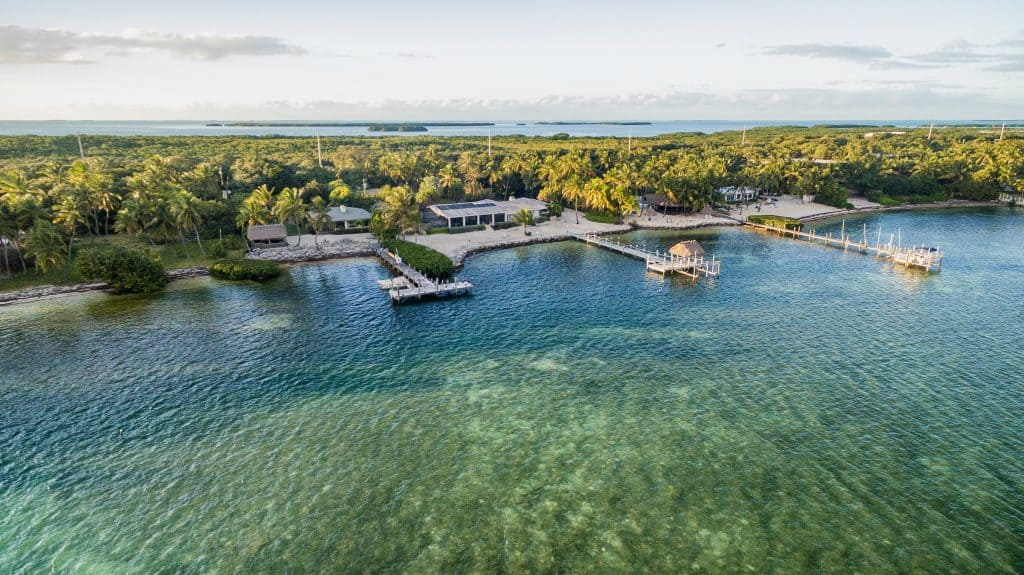 An aerial drone captures the blue-green waters and docks of Islamorada, one of the cutest small towns in the Florida Keys.