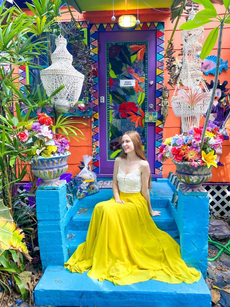 Victoria sits in a vibrant yellow skirt on the blindingly colorful decorations of Whimseyland in Safety Harbor.