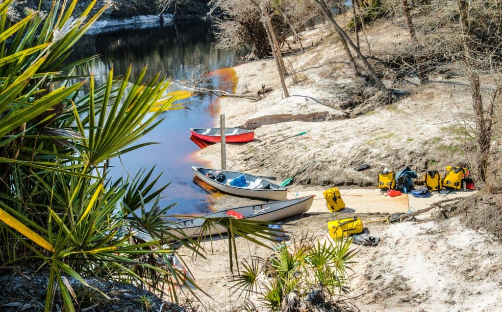 Canoes and backpacking gear sit ready on the shores of Stephen Foster Folk Culture State Park in White Springs, one of the cutest small towns in Florida.