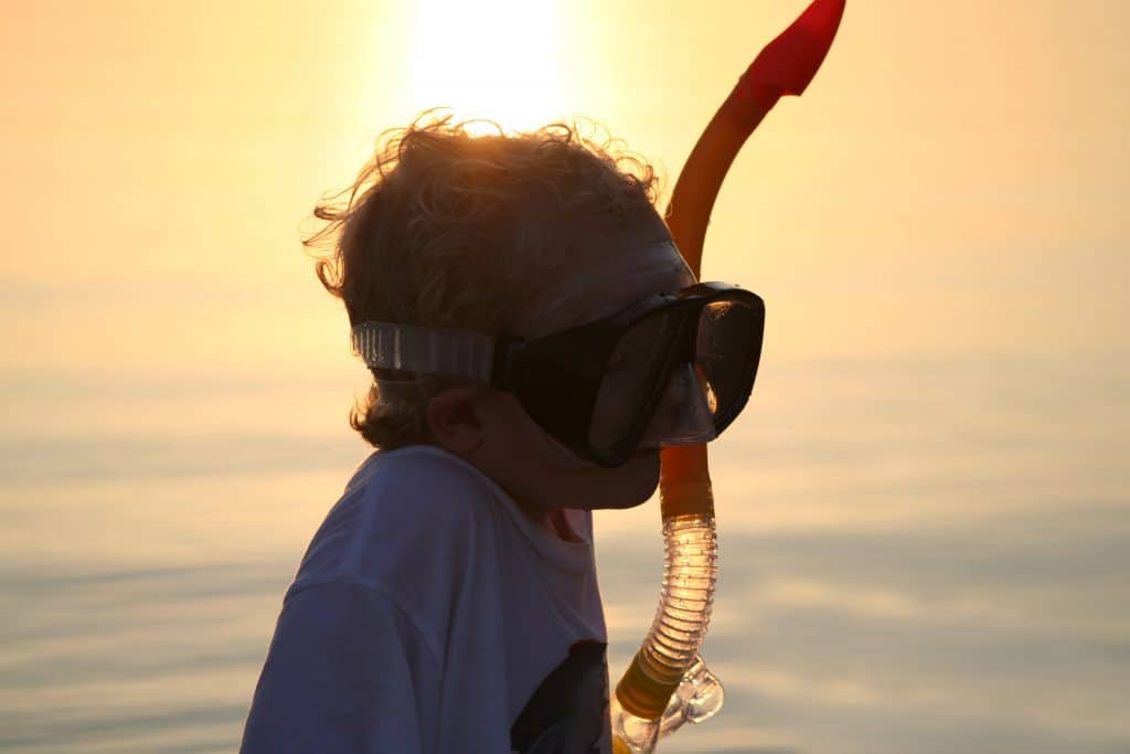 A child dons a snorkel and mask in the sunset of the Florida Keys.
