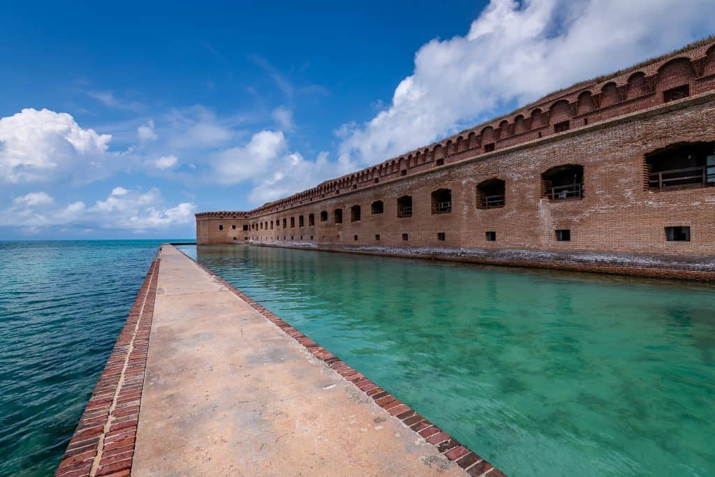 A walkway through the water surrounds Fort Jefferson at Dry Tortugas National Park, one of the best things to do in the Keys.