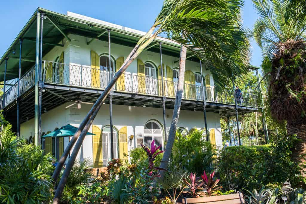 The colorful exterior of the Ernest Hemingway Home and Museum with beautiful verandas, palm trees blowing in the breeze.