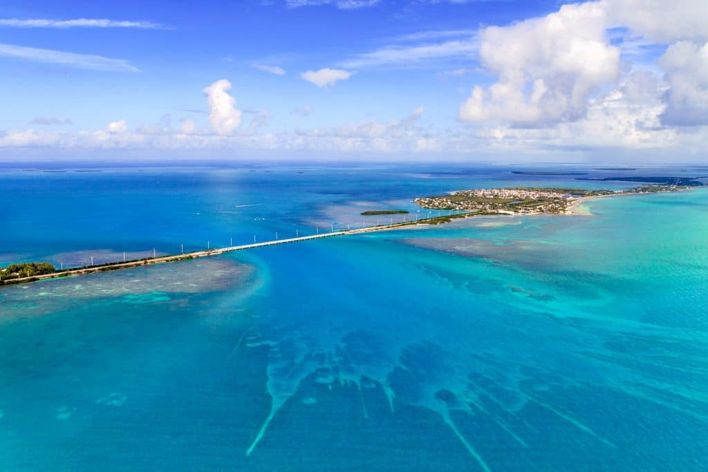 An aerial shot of the Seven Mile Bridge connects the Florida Keys together, surrounded by piercingly blue ocean waters.