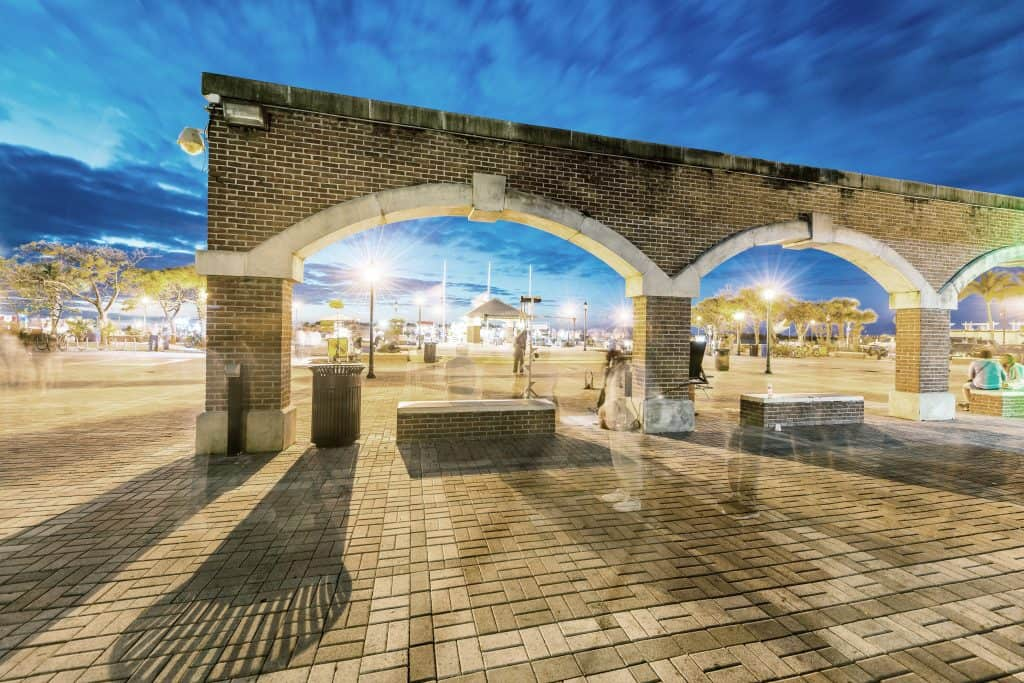 The arches of Mallory Square, one of the best things to do in the Keys, glimmer in the night lights.