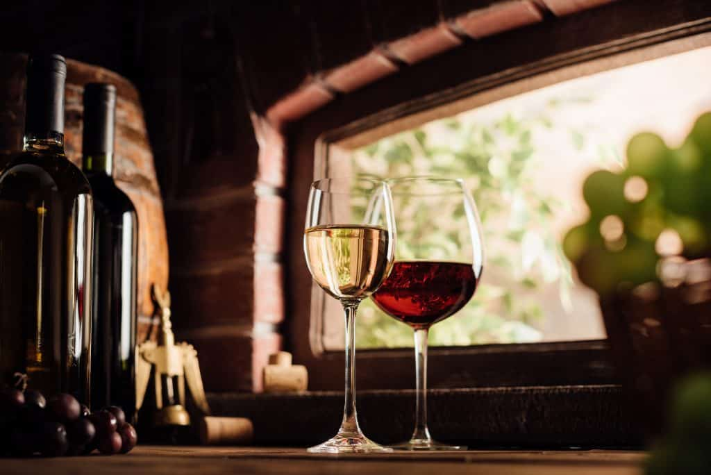 A glass of red and white wines sit in the window at one of the best wineries in Florida.
