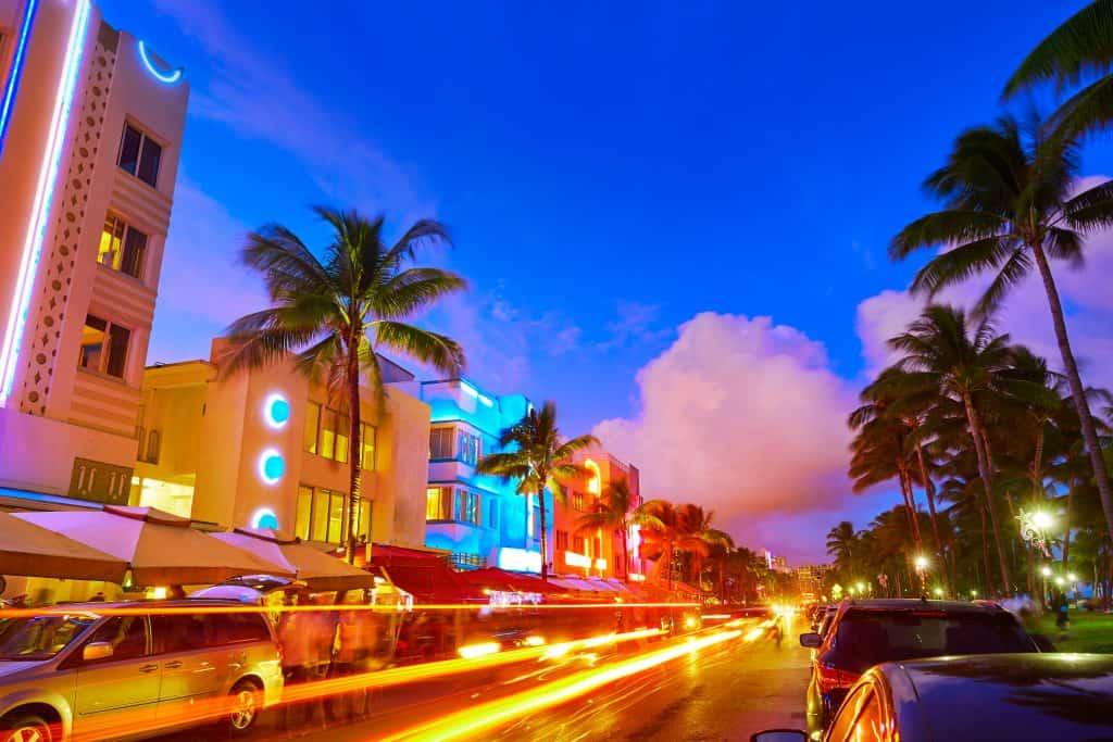 Cars rush down a street lined by colorful buildings in Miami Beach, one of the best day trips from Naples.