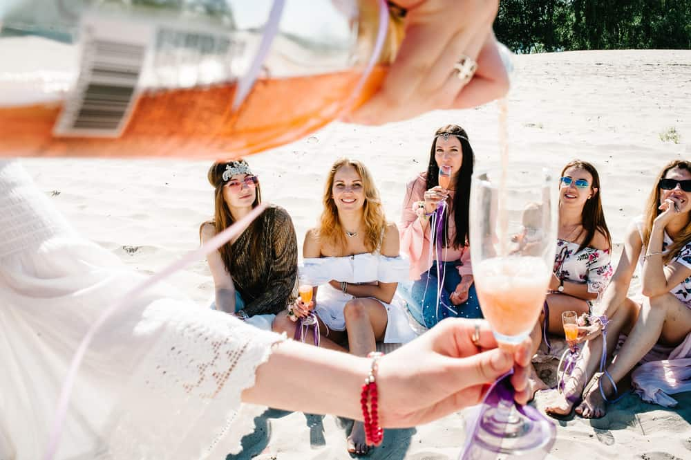 Hand pours champagne into glass in foreground with happy group of girls in background at a Florida bachelorette party