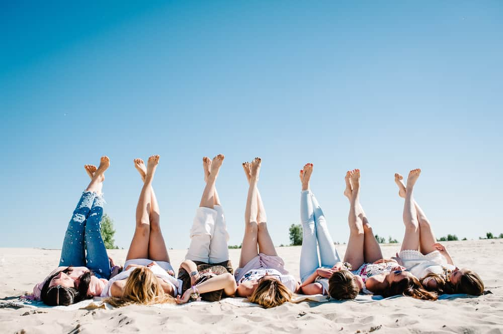 Seven girls on the beach with their legs crossed and in the air. Article is about Florida Bachelorette Party