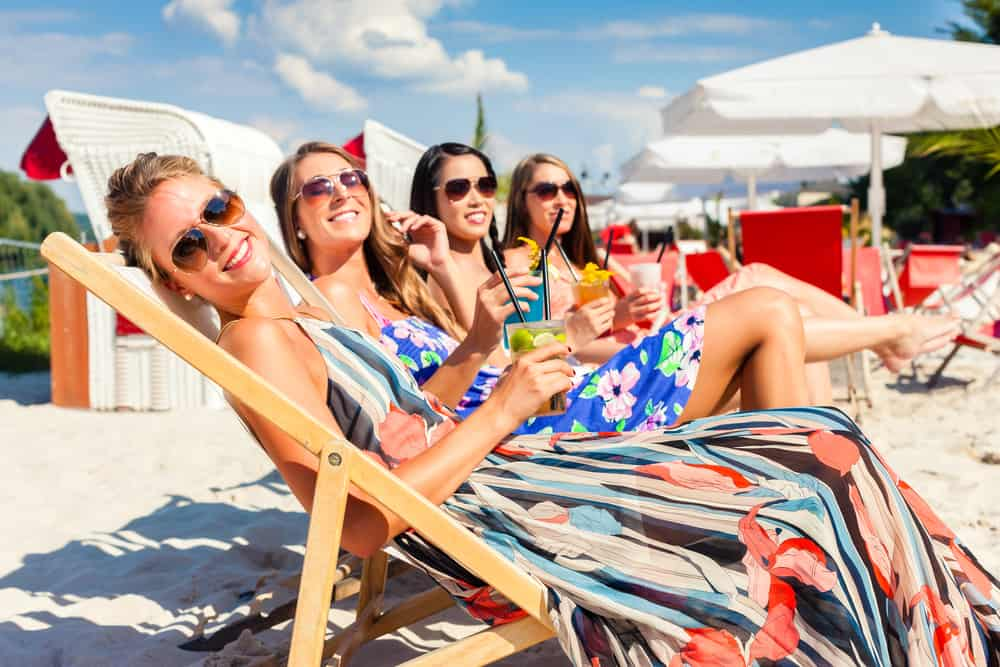 Four girls laid on the beach on sun loungers smiling at the camera in an article about Florida Bachelorette Party