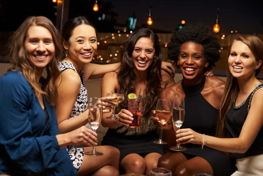Five girls having a Florida Bachelorette Party at a bar with drinks smiling at camera
