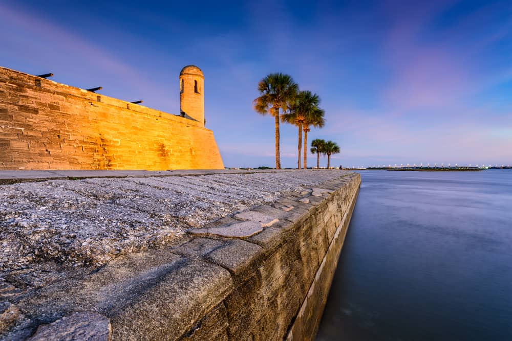 A small, stone Florida castle at sunset next to the water, with palm trees beside it