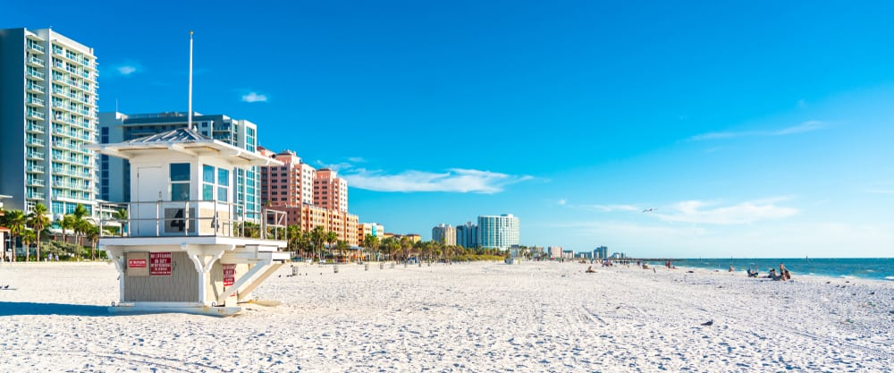An empty, Clearwater shore aside a hotel strip with blue skies