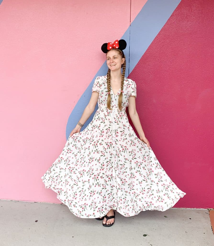 A woman in a floral dress and Minnie Mouse ears in front of the bubblegum wall in Walt Disney World's Epcot