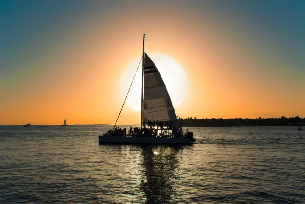 A catamaran sails on the bay at sunset during one of the best Naples boat trips.