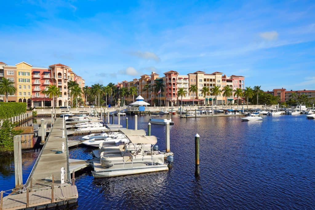The Naples bay marina shimmers with its colorful buildings in the background.