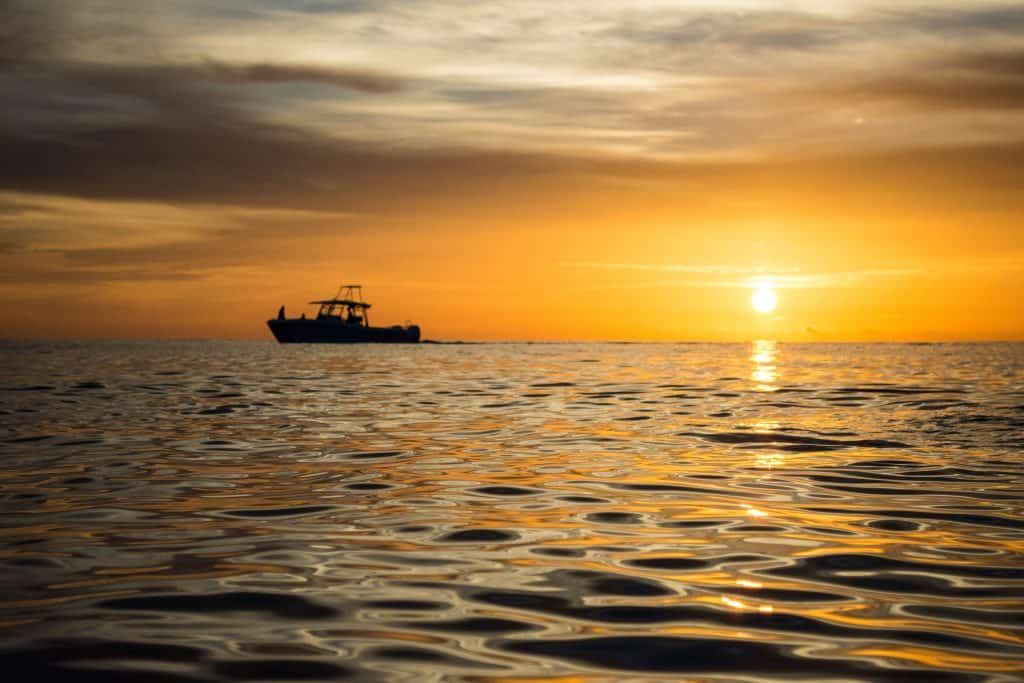 A tour boat glides along the water at sunset in Naples.