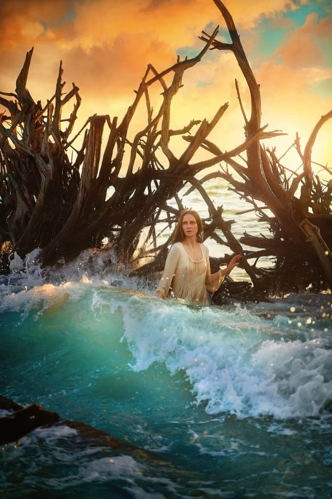 Victoria wades through the waves in front of driftwood at Beer Can Island, one of the best things to do in Siesta Key.