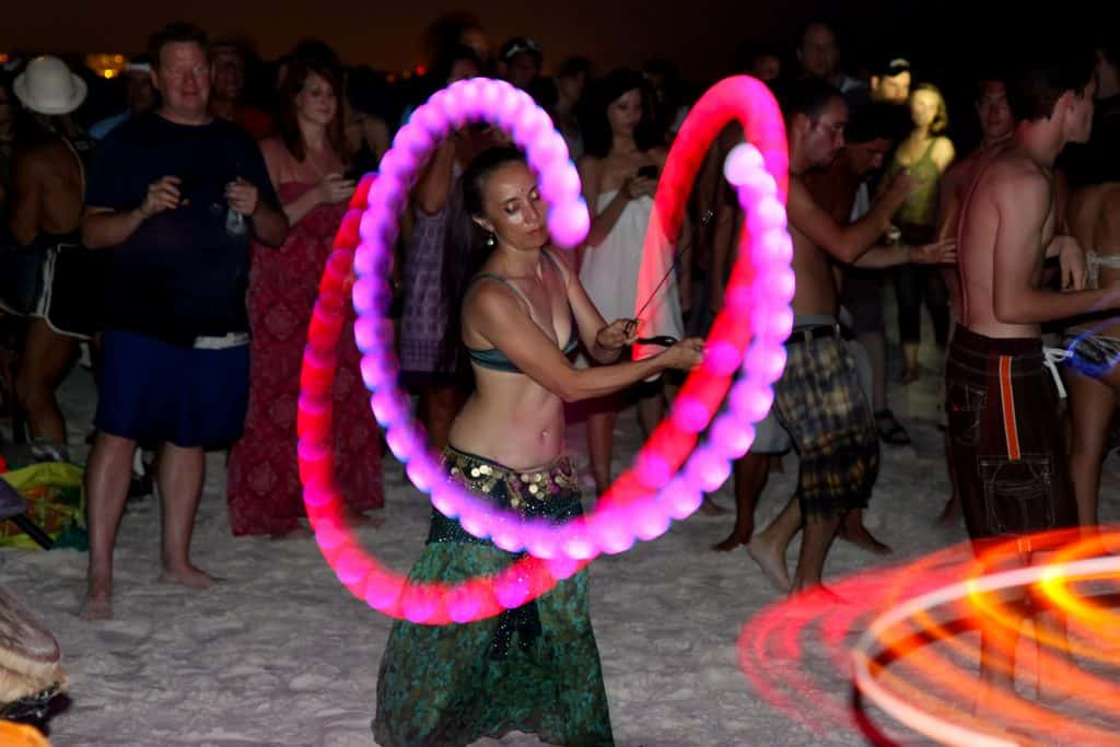 A dancer twirls lights while belly dancing during the Siesta Key Drum Circle.
