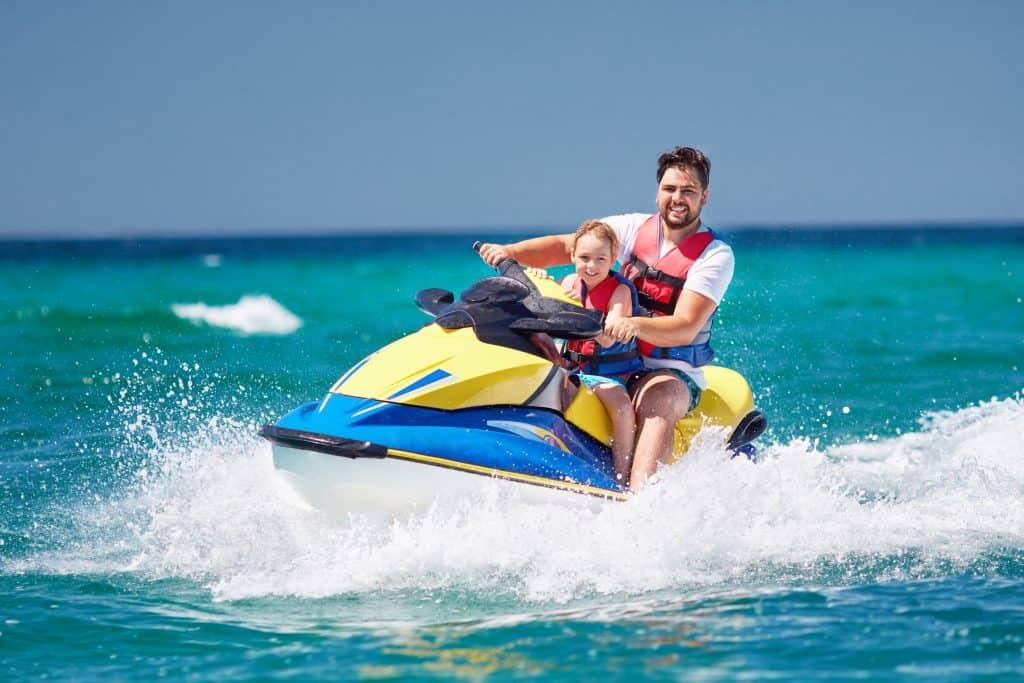 Tourists enjoy riding a jet ski on the waves, courtesy of Siesta Key Watersports.