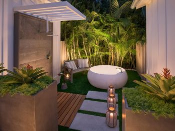 A outside tub and shower surrounded by green foliage