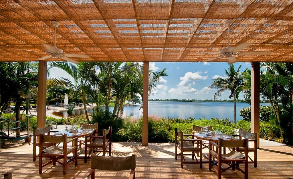 An outdoor dining area looking over water at one of the all inclusive resorts in Florida