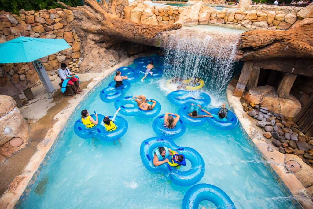 People in inflatable tubes wading under a waterfall through a lazy river.