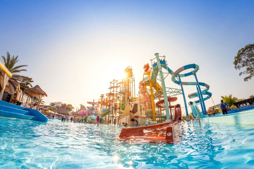 An abundance of waterslides overlooking a swimming pool on the verge of sunset