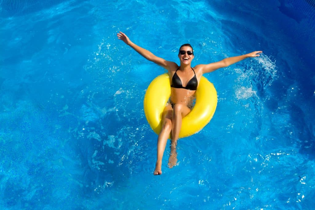 A woman in a yellow tube floating in a pool