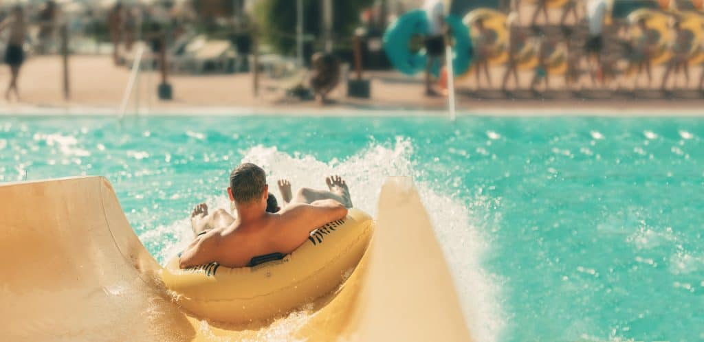 A man in a yellow tube going down a waterslide
