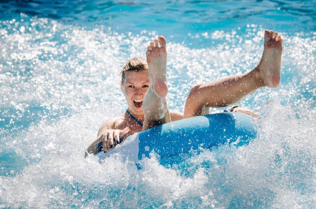 A woman in a blue tube caught in a wave