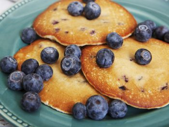 blueberry pancakes on a plate with syrup