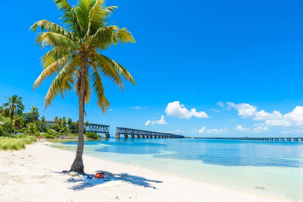 The beautiful beach of Bahia Honda with the old bridge in the background, one of the most perfect day trips from Miami.