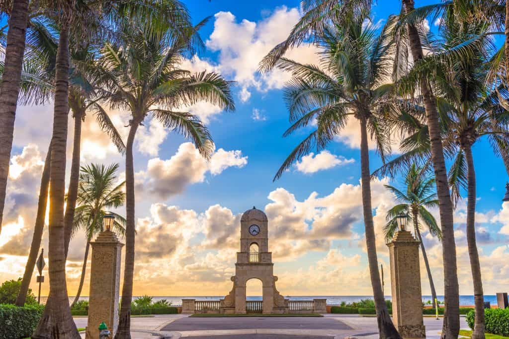 The clock tower stands against the sun setting in West Palm Beach.