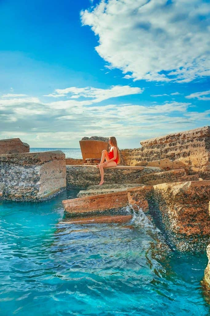 Girl in red swimsuit sitting on the portion of Battery Bigelow fort that juts up out of the  turquoise water