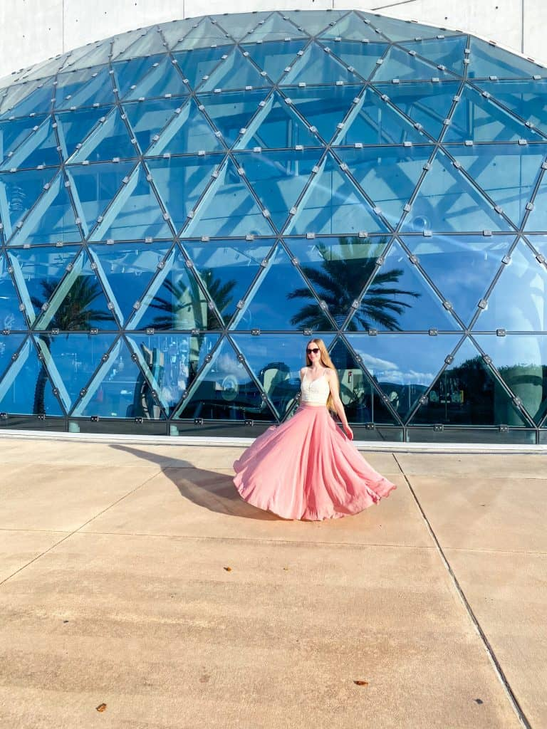 Girl in a pink long skirt poses in front of the glass dome of the Dali Museum in St. Pete