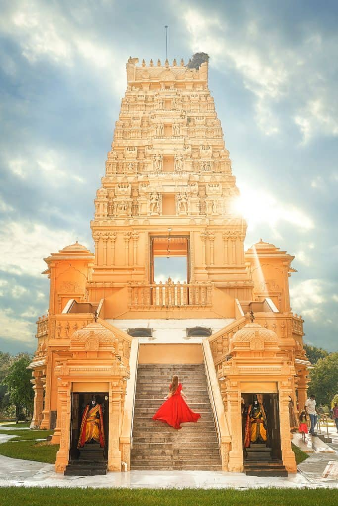 Girl in red dress posses on the steps of the religious Hindu Temple in Florida