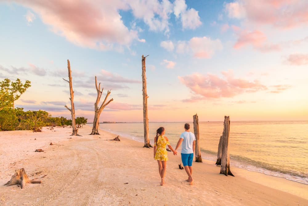 couple walking along the beach at sunset on lovers key