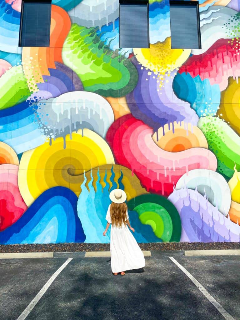 At this St. Pete Florida instagrammable spots a girl in a white dress and hat poses in front of a multicolored street art mural